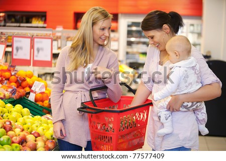 Mother carrying child with friend while shopping in supermarket