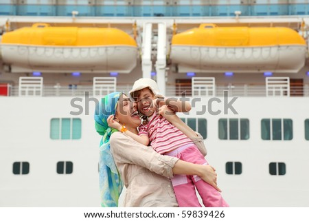 mother carrying her daughter and laughing, big cruise ship on background