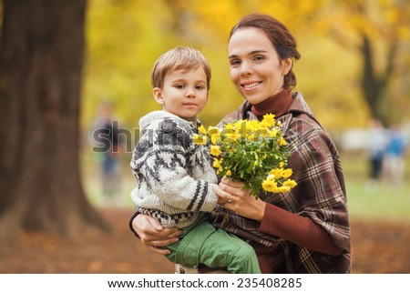 Mother carrying her son in one hand and flowers in the other hand