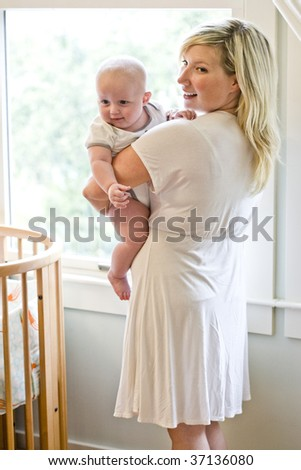 Mother carrying seven month old baby beside crib