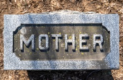 Mother carved in the top of a tombstone. Close up high angle view in natural light.