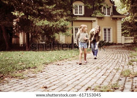 Mother catching cheerful girl outdoor. Focus is on girl in the front.