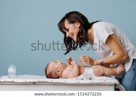 Mother changing diaper on her baby on table over blue background. They look at each other, smile and laugh. Foto stock ©