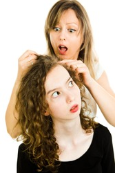 Mother checking child's head for lice showing emotion of surprise, consternation and dismay - louse on head, curly hairs - white background
