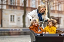 Mother checking on her children who is riding in the front section of a cargo bike