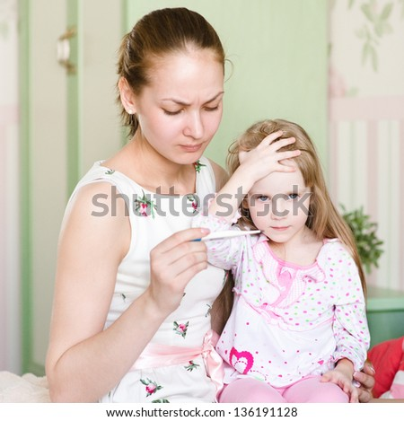mother checks temperature at the sick child
