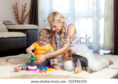mother, child boy and pet dog playing toy together indoor