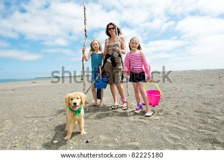 Mother, children and puppy at the beach