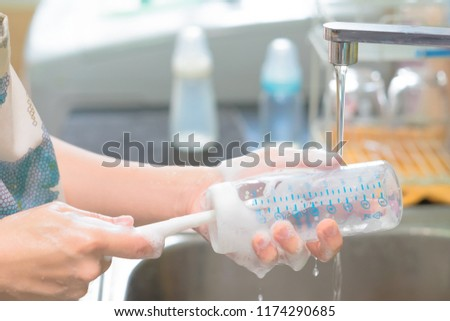 Mother cleaning baby milk bottles with bottle brush. Selective focus. Copy space.