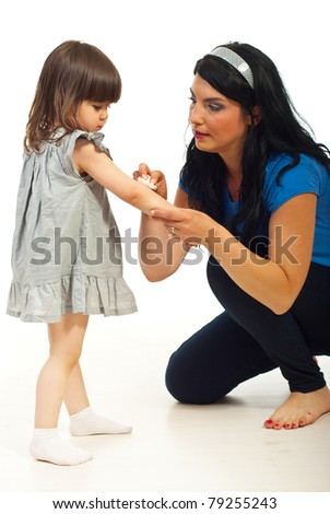 Mother cleaning wound to her toddler daughter  and  sitting on floor over white background