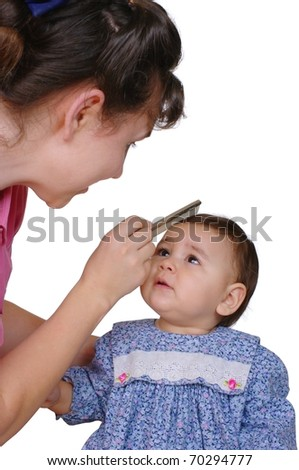 Mother combing one-year-old baby daughter's hair, isolated on pure white background