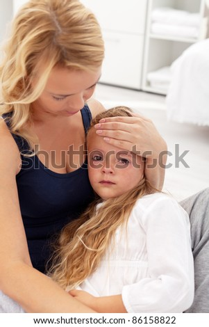 Mother comforting her upset or sick little girl