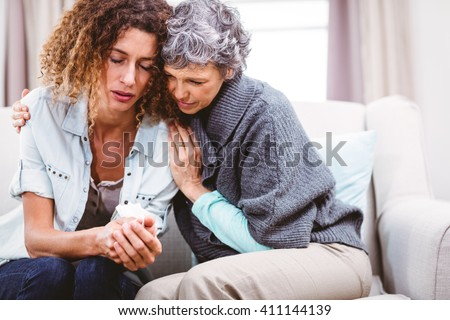 Mother comforting tensed daughter sitting on sofa at home