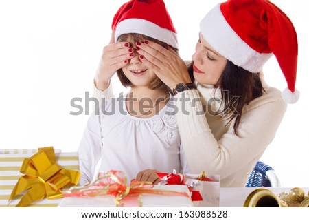 Mother covering daughter eyes with hands hiding Christmas gifts over white