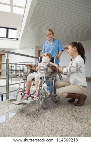 Mother crouches next to her child in wheelchair with nurse pushing it in hospital corridor