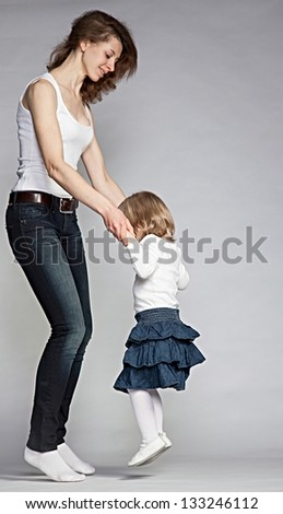 Mother dancing with her little daughter, grey background
