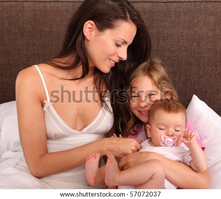 mother daughter and baby in bed- family lifestyle
