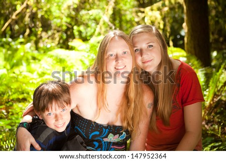 Mother, daughter and son in sunny and green summer forest. Shallow DOF, mother's face in focus, boy slightly soft.