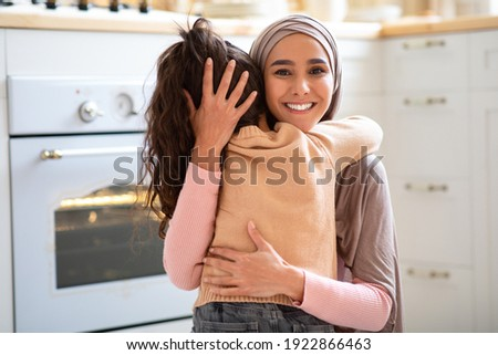 Mother Daughter Love. Beautiful Muslim Lady In Hijab Embracing Her Little Child In Kitchen Interior, Small Girl Hugging Her Happy Islamic Mom At Home, Greeting With Mother's Day, Free Space
