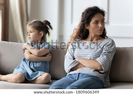 Mother disobedient daughter sit apart on sofa with arms crossed posture of discontent, think feels frustrated. Challenges of kids raising, lack of emotional bonding, child-rearing difficulties concept Photo stock ©