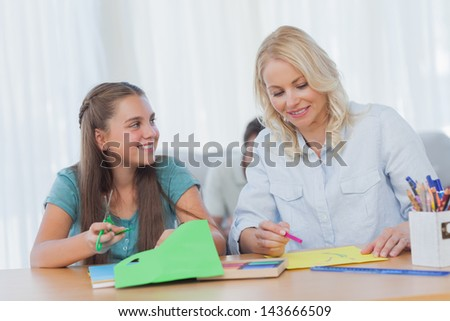 Mother doing arts and crafts with her daughter at home in living room