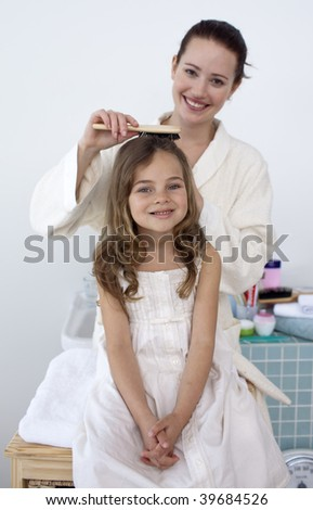 Mother doing her little daughter's hair in bathroom