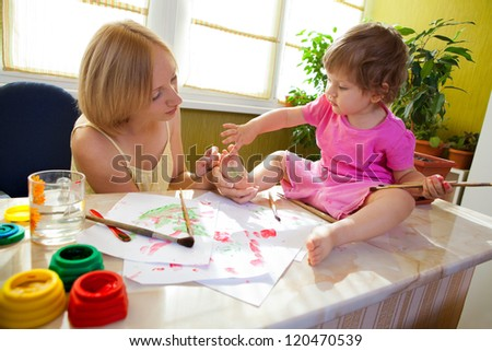 Mother drawing a flower on her daughter heel