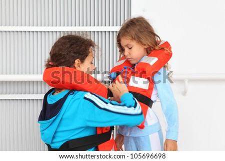 Mother dresses her daughter in orange life jacket at deck of ship