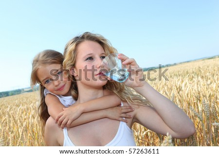 Mother drinking water in wheat field with child
