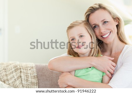 Mother embracing daughter on the couch