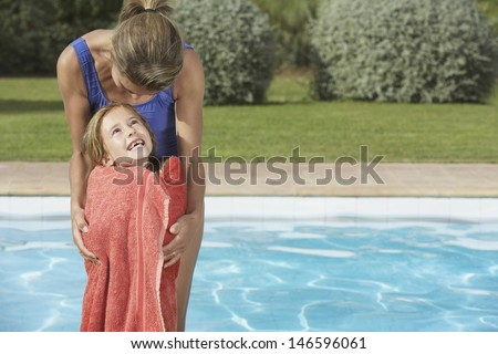Mother embracing daughter wrapped in towel against swimming pool