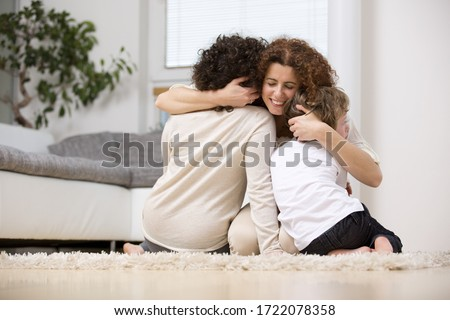 Mother embracing son and daughter on rug in living room