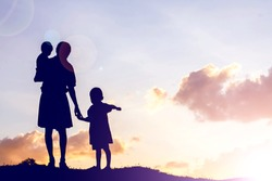 Mother encouraged her son outdoors at sunset, silhouette concept