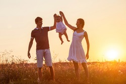 Mother, father and child daughter having fun outdoors.