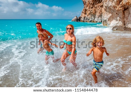 Mother father and children are running on summer beach.  Stock foto ©