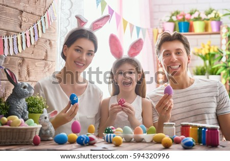 Mother, father and daughter are painting eggs. Happy family are preparing for Easter. Cute little child girl wearing bunny ears. #594320996