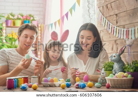 Mother, father and daughter are painting eggs. Happy family are preparing for Easter. Cute little child girl wearing bunny ears. #606107606