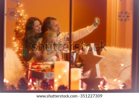 Mother, father and daughter celebrating Christmas at home, looking through the window.  Making pictures.  #351227309