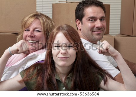 Mother, father and daughter leaning on moving boxes.