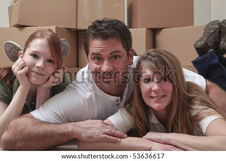 Mother, father and daughter lying on the floor in front of moving boxes.