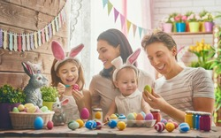 Mother, father and daughters are painting eggs. Happy family are preparing for Easter. Cute little child girl wearing bunny ears.