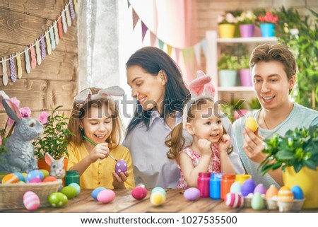 Mother, father and daughters are painting eggs. Happy family are preparing for Easter. Cute little children girls wearing bunny ears. #1027535500
