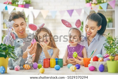 Mother, father and daughters are painting eggs. Happy family are preparing for Easter. Cute little children girls wearing bunny ears. #1029370294