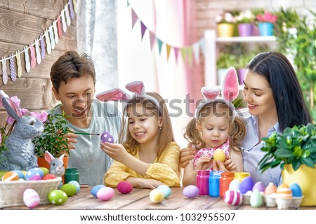 Mother, father and daughters are painting eggs. Happy family are preparing for Easter. Cute little children girls wearing bunny ears. #1032955507