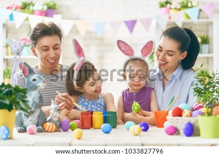 Mother, father and daughters are painting eggs. Happy family are preparing for Easter. Cute little children girls wearing bunny ears. #1033827796
