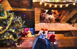 Mother father and kids sitting at cosy fireplace on winter time - Lovely family resting together on woolen socks at home fire place - Christmas holidays concept on comfy house venue - Warm filter