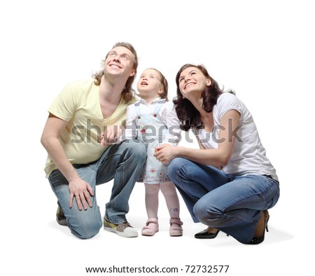 Mother, father and little daughter sit down, hold hands and fixedly looking up with smile