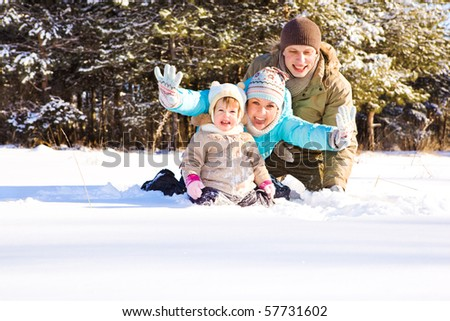 Mother, father and little girl in snow
