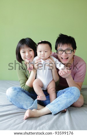 Mother, father and small baby smile face with green background. Model are asian family.