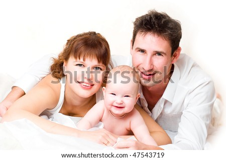 Mother,  father and small daughter laugh, lying on a floor. High key  portrait
